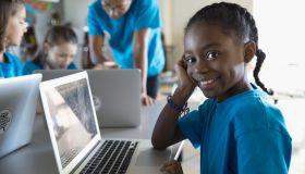 Portrait confident, smiling pre-adolescent girl using laptop in classroom