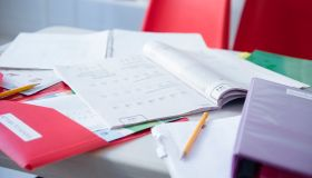 Workbook and folder on desk in classroom