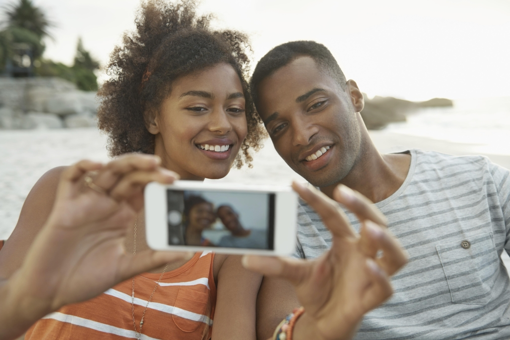 A young couple taking a selfie with a smartphone camera