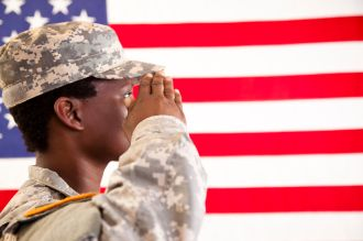 African descent military woman salutes American flag.