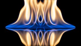 Flames of orange and blue with reflections on a black background color