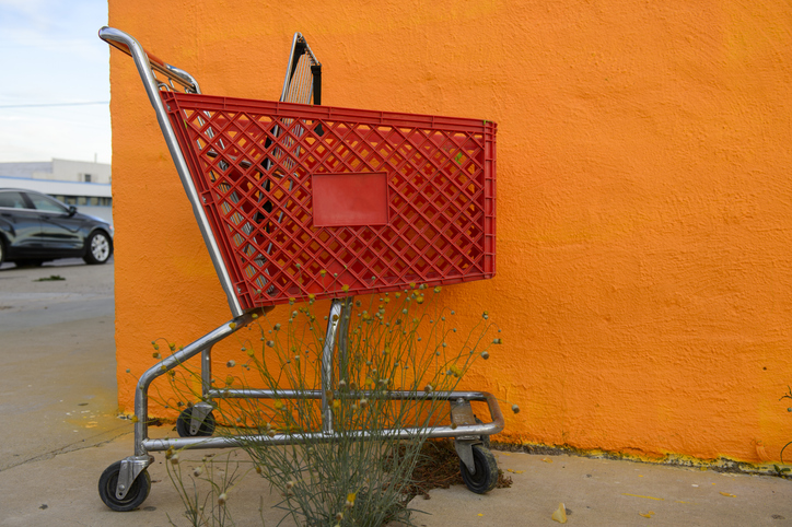 A red shopping cart in front a orang colored wall at Fort Stockton, Texas, USA