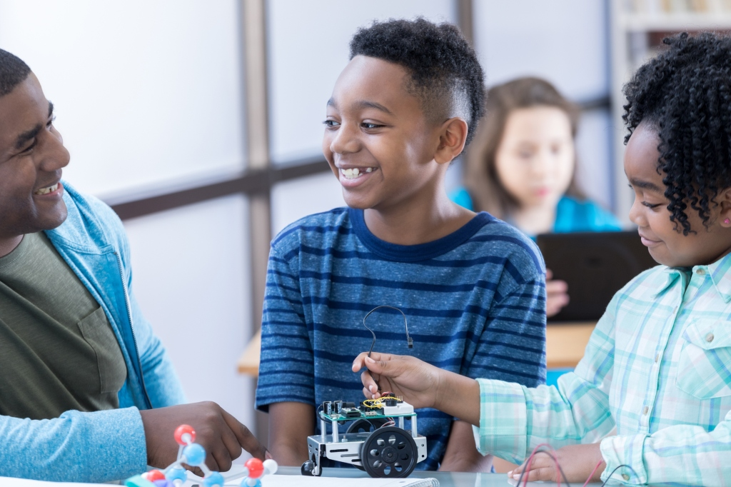 Two students work on robotics project at school with dad
