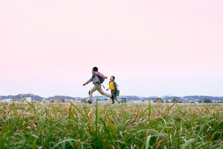 Young boys running at riverbank.