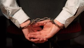 The picture shows hands handcuffed together. The person is wearing a business sh