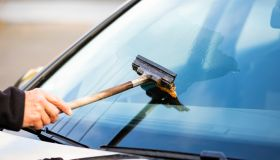 Cropped Hand Cleaning Car Windshield