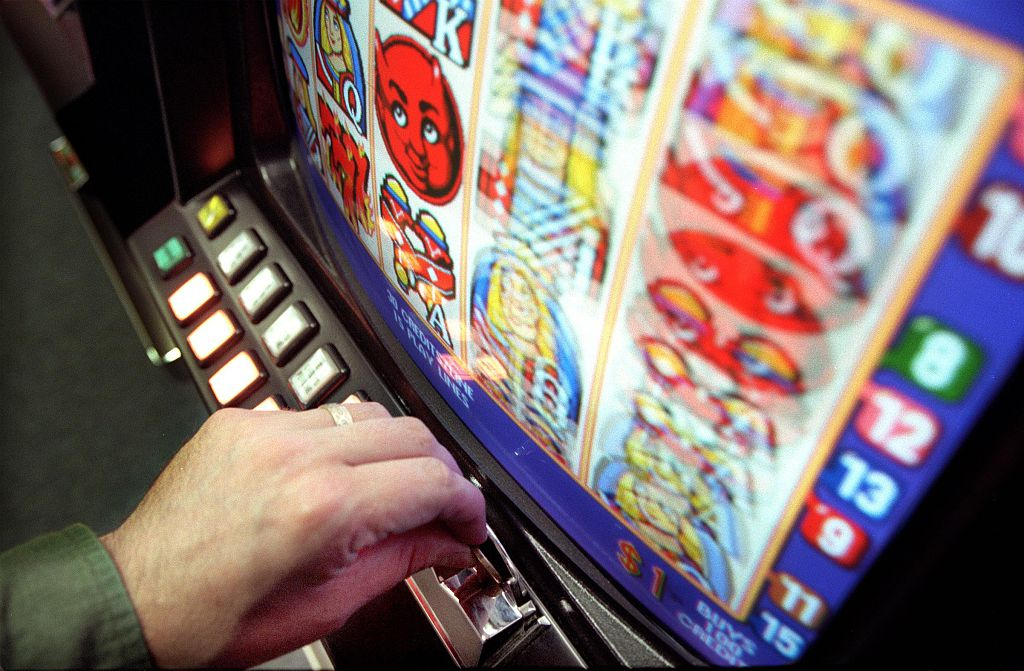 A gambler plays a poker machine, 13 November 2006. AFR Picture by PHIL CARRICK