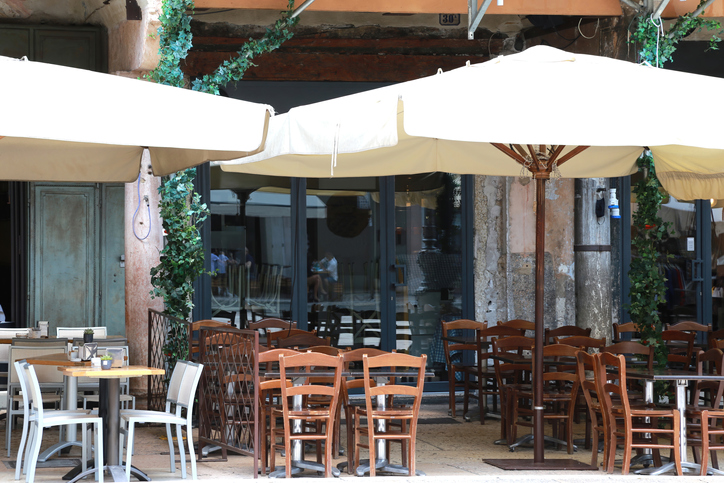 Empty outdoor tables of a Pizzeria - Osteria in Verona