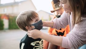 Mother putting protective face mask on her child during COVID-19 pandemic on Halloween