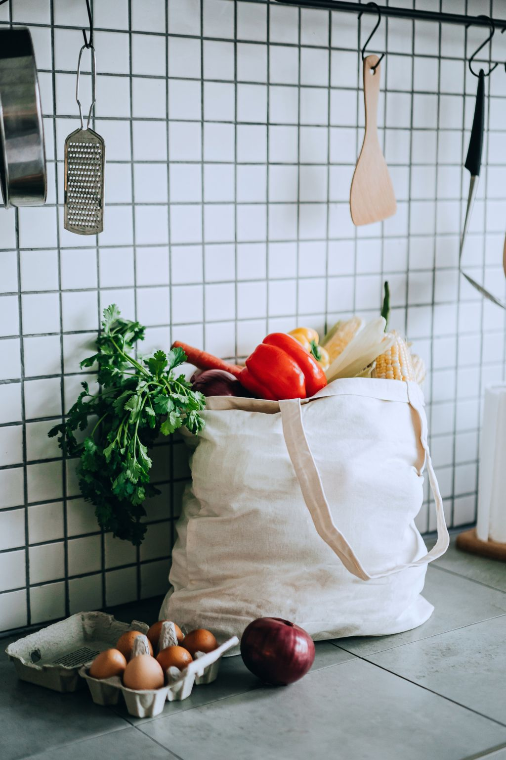 A reusable bag full of colourful and fresh organic vegetables and groceries on the kitchen counter. Zero waste shopping and sustainable lifestyle concept
