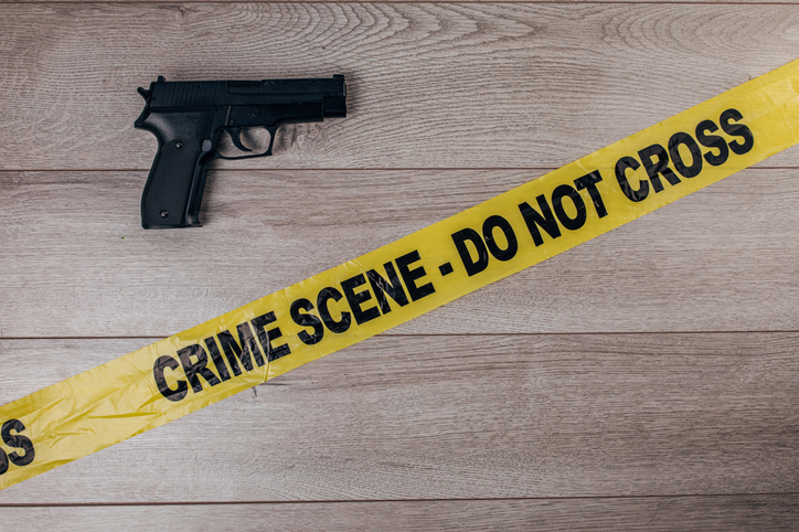 Crime scene tape and gun on wooden background