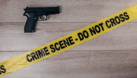 Crime scene tape and gun on wooden background