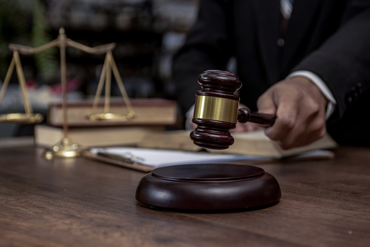 Man hand knocking a wooden judge gavel, law and auction concept.