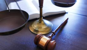 Gavel Rests In Front of Justice Scale And Open Law Book