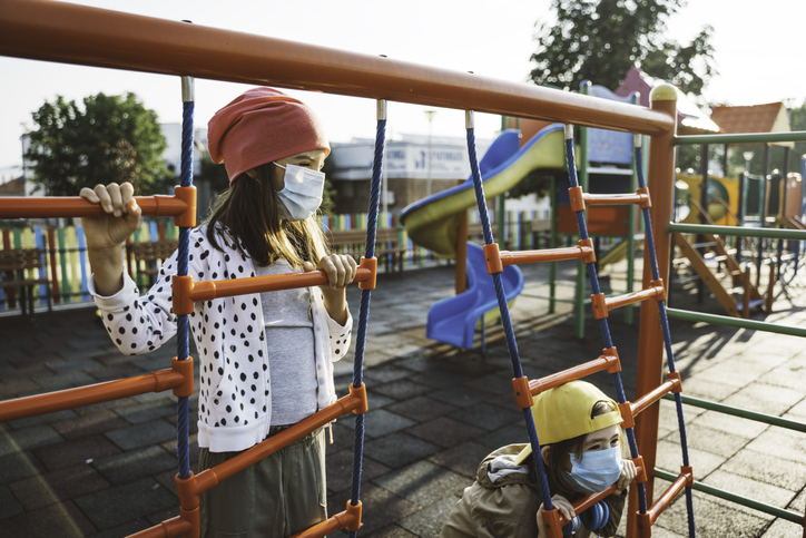 Kids with face protective mask are having fun on the playground. COVID-19, Coronavirus epidemic. New normal. Smiling behind the mask.
