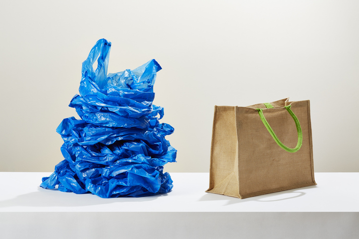 A stack of plastic carrier bags next to a reusable shopping bag