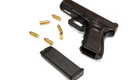 High Angle View Of Hand Gun And Bullets Against White Background