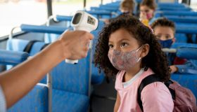Girl getting her temperature checked on the school bus